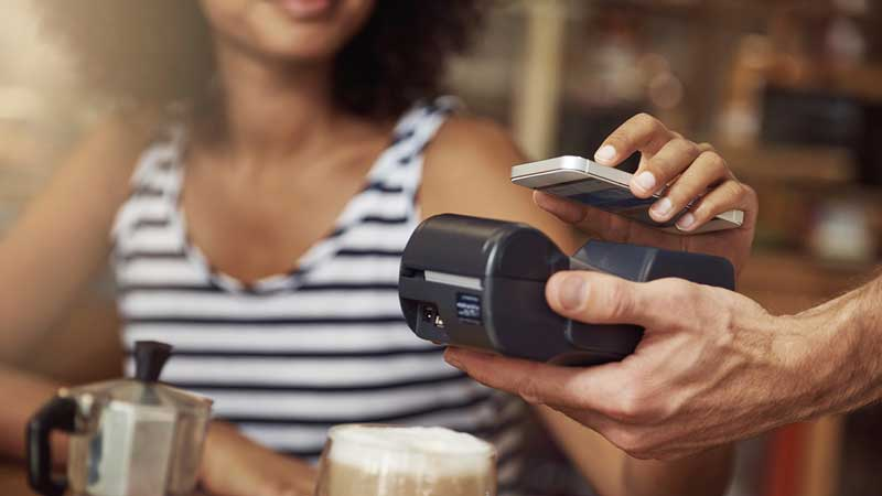 A woman at a café make a contactless payment on a card reader using her device.
