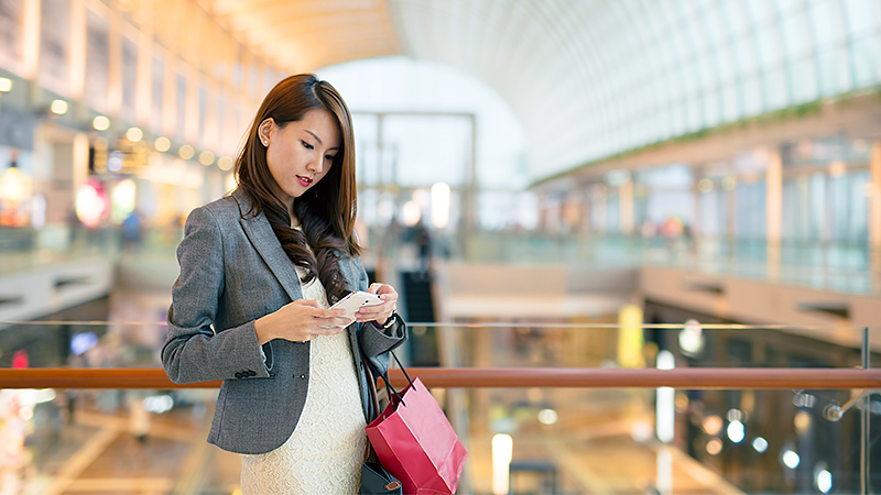 woman checking her phone inside a shopping area