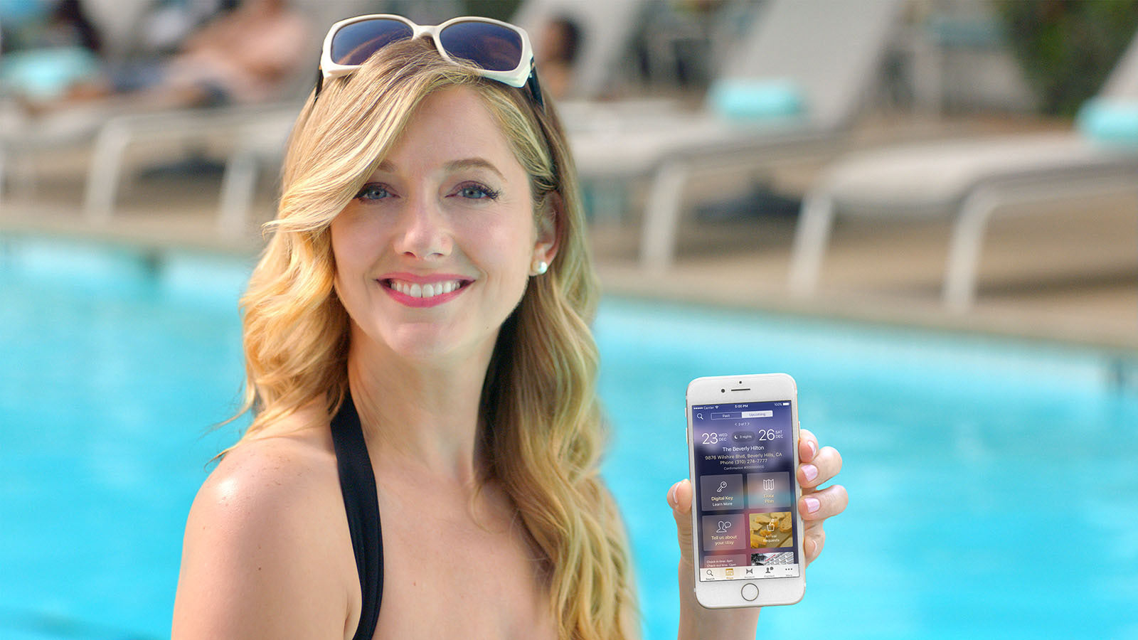 woman holding a phone next to a swimming pool