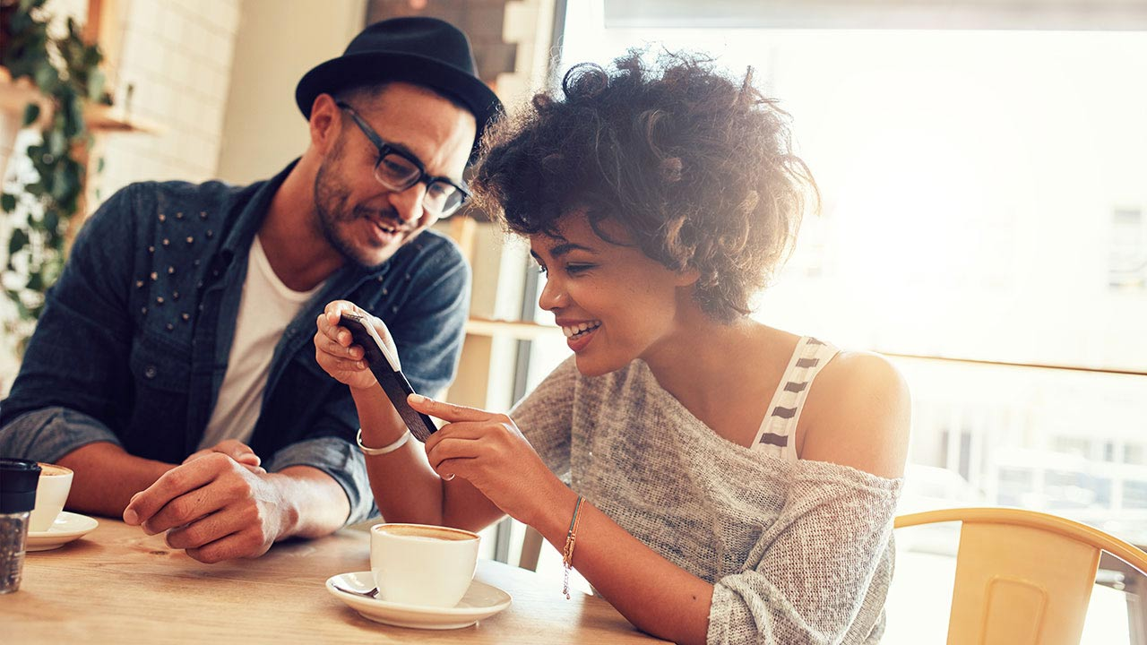 Smiling couple seated at table in café looking at mobile phone.