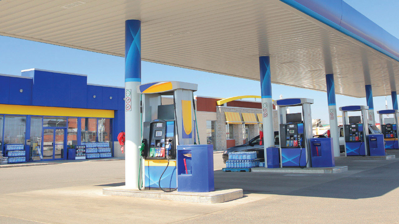 Gas station store front with row of gas pumps in foreground.